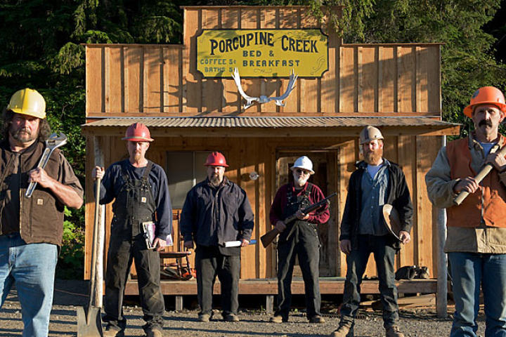 The miners take their stand in front of their Porcupine Creek headquarters, built shortly after they first took possession of their claim. As a tribute to the first generation of miners who came to Porcupine Creek in the late 1890's, the 21st century crew put up a sign offering the going rate for coffee and a bath over century ago.