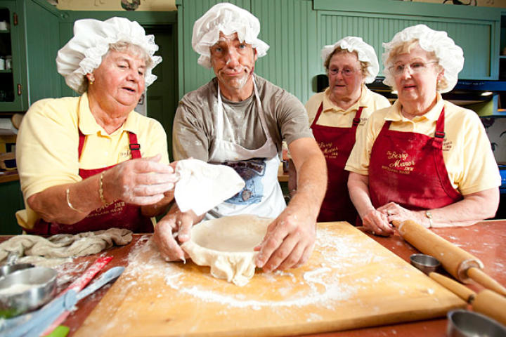 """The """"Pie Moms"""" welcome Mike Rowe and his 8 pounds of blueberries to the Berry Manor Inn in Rockland, Maine. Ally Taylor and Janet LaPosta, the mothers of Cheryl Michaelsen and Mike LaPosta, owners of the Berry Manor Inn, have each been making pies for more 50 years."""