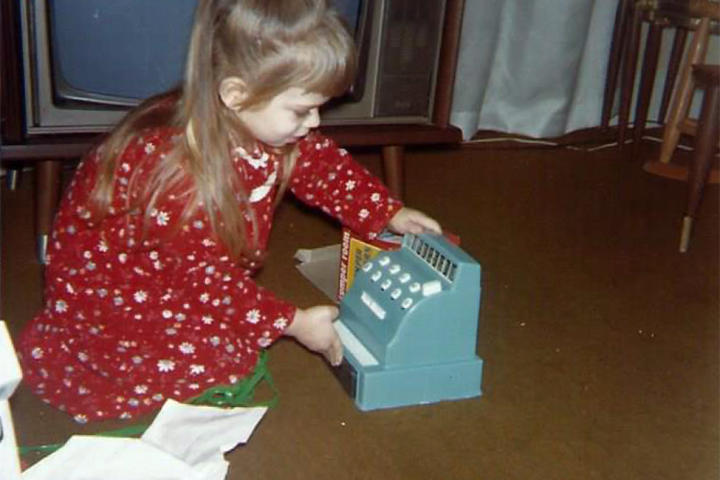 Theresa unwraps a toy register on Christmas day.