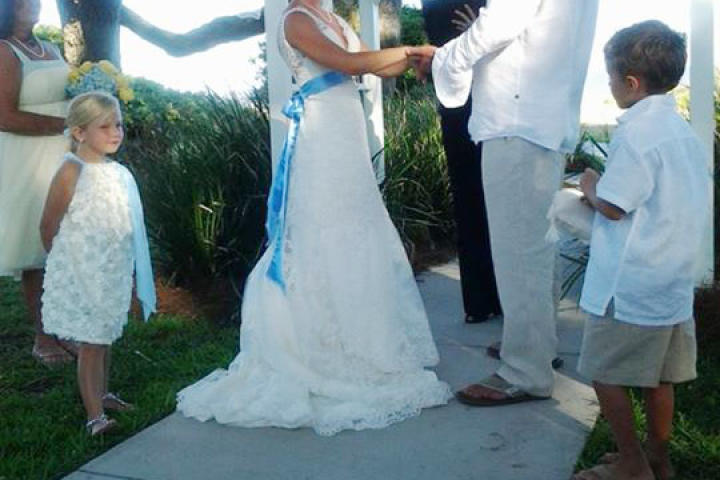 Ansley wears bright white lace, and her groom also wears light-colored attire for their beach wedding.