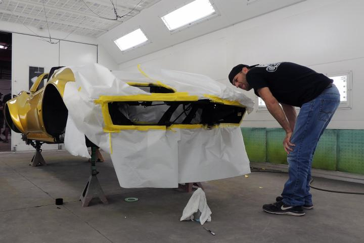 Jason Aker surveys the 1968 Gold Corvette during its exterior transformation from black to gold.
