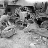 The crew of a Sherman tank of the British Westminster Dragoons repairing damage to one of its suspension units caused by an 88mm anti-tank shell, June 7, 1944, a day after the beginning of the D-Day landings. Watch video of the