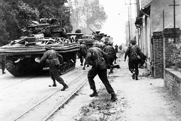 Action shot of house-to-house fighting by British Commandos supported by Sherman tanks, at Riva Bella, near Ouistreham. This engagement was featured in the movie The Longest Day.