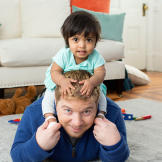 Zoey happily sits on Dad's shoulders.