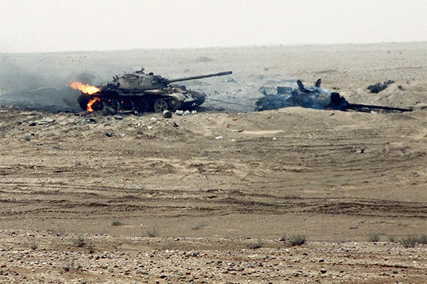 Still burning, these two Iraqi T-55 main battle tanks were damaged by a Coalition attack near the Kuwait border during Operation Desert Storm. The rear tank was attempting to tow the other one, as evidenced by the cable linking them, February 1991. Watch