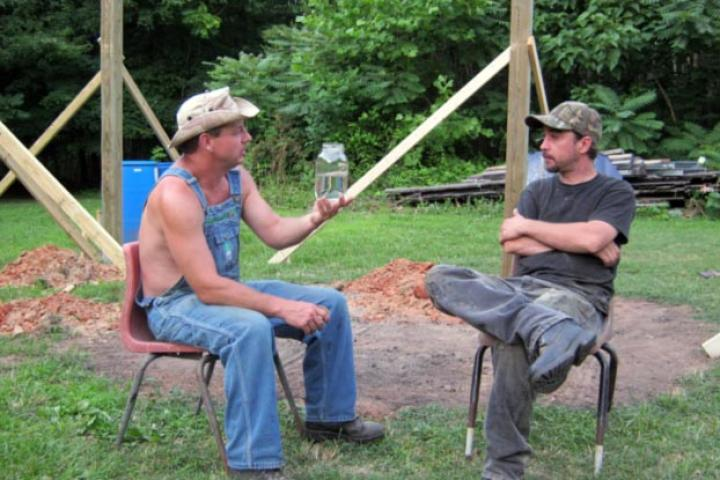 Tim shows off a jar of moonshiner to Tickle.