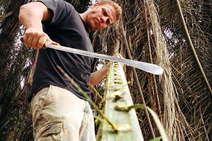 George uses a machete to get through the tough jungle.