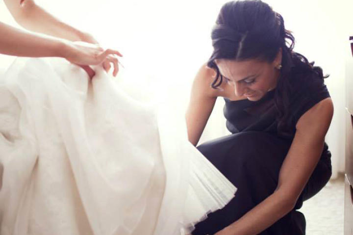 Bridal attendants are there to support you in every way possible, from throwing the bachelorette party to buckling your sandal!