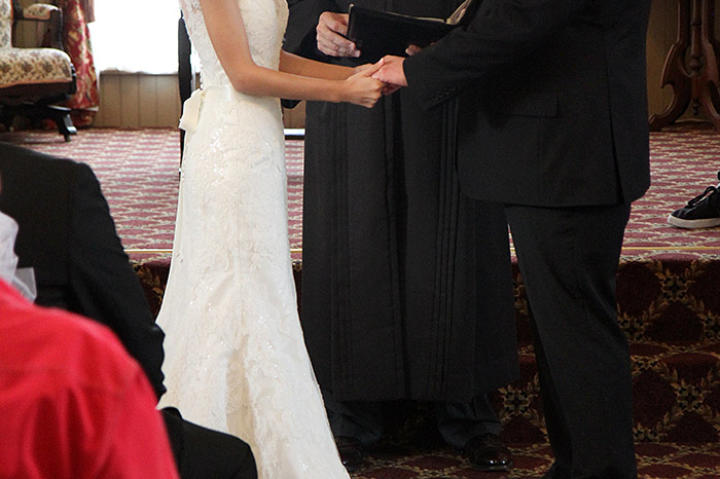 Mike and Aziza hold hands during their wedding vows.