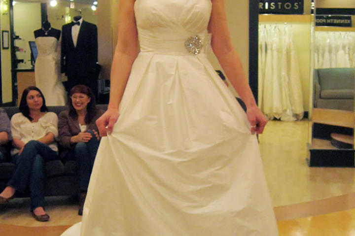 An architectural ivory ball gown with pleated neckline and structured skirt gets a boost of formality in ivory.