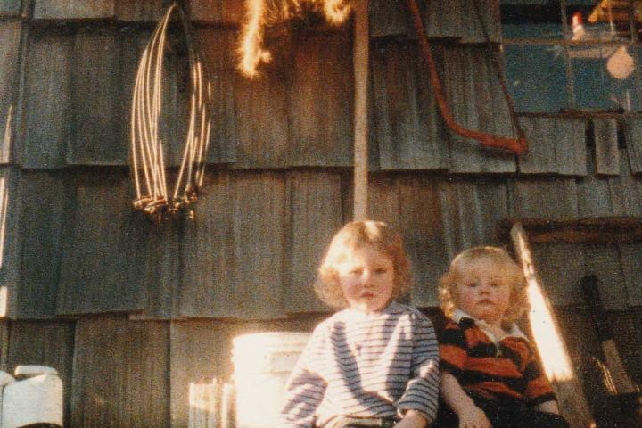Matt and Bam Bam sit in front of their old cabin as babies. Look at those blonde curls!