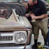 Dustin DeLeon works on the hood of the 1965 Chevy C-10 pickup truck ba