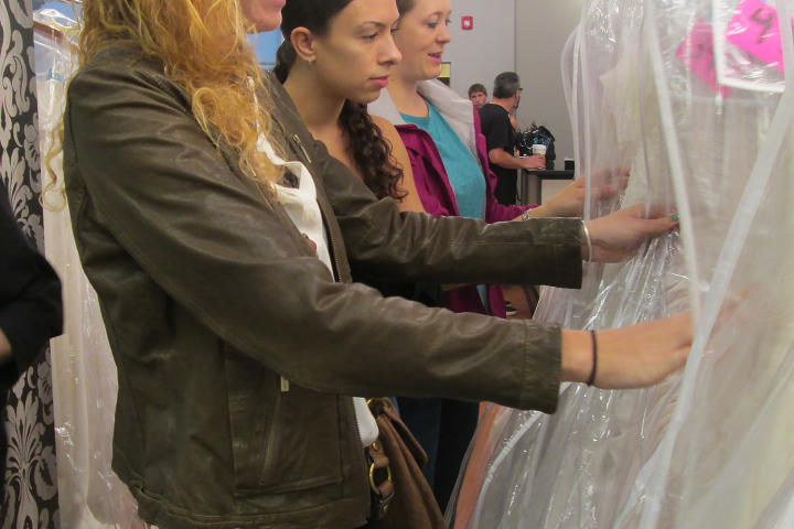 Once the doors open, brides run inside to start sifting through the racks and racks and racks of dresses.