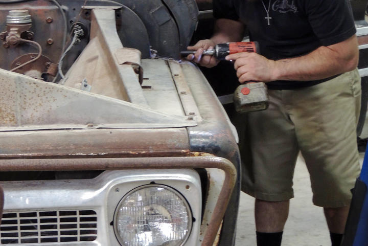 Dustin DeLeon works on the hood of the 1965 Chevy C-10 pickup truck back at the garage.