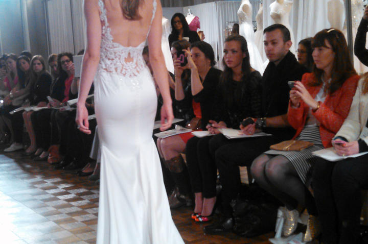 """Body-conscious fits and matte fabrics ruled the runway. """"These collections were all about the back,"""" Monte says. """"Brides have been begging for two things: sexy backs and straps. These gowns offered both. Straps are a must because if you go low in the back, you have to support the front somehow!"""" This tank dress by Watters has beaded open latticework in the back."""