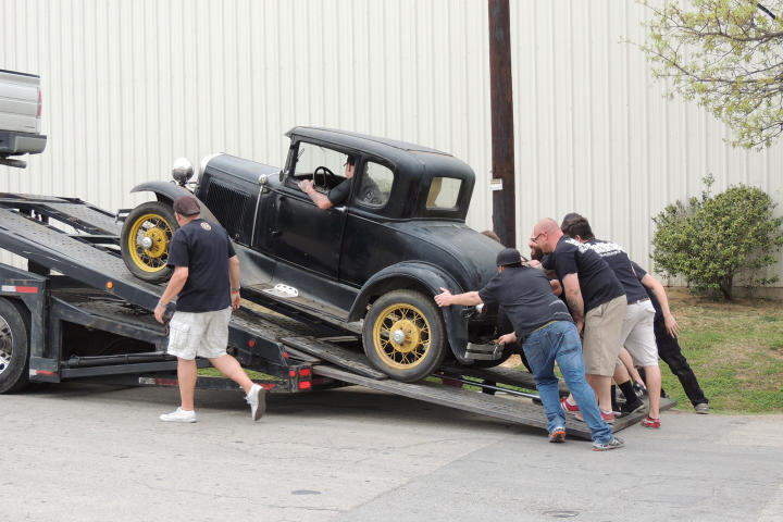 Tony Taylor observes as KC Mathieu, Mike Coy, Dustin DeLeon and several other Gas Monkies help unload the 1931 Model A.