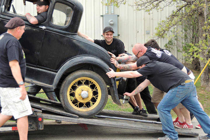 Tony Taylor observes as KC Mathieu, Mike Coy, Dustin DeLeon and Josh Anderson steady the Model A as it comes off the trailer.