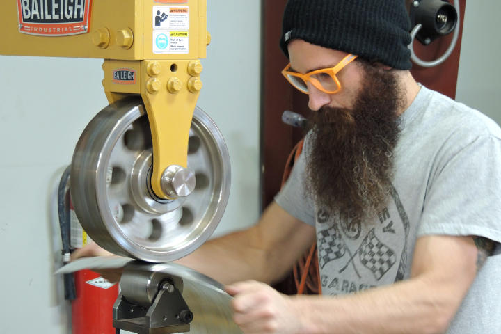 Aaron Kaufman, wearing orange glasses, runs sheet metal through a machine.