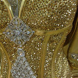 The bodice of Kayla's dress is covered in gold Swarovski crystals that Sondra special-ordered from Austria.