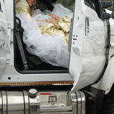 It wasn't easy, but Kayla stuffs herself into the passenger's seat of a monster truck wearing her wedding dress.