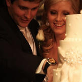 """Holly and Robert cut the bride's cake while """"So This Is Love&quot"""
