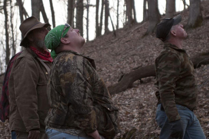 Trapper (left), Buck (center) and Wild Bill watch as Willy climbs a tree.