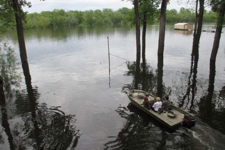 When living in the bayou, boat transportation is crucial. Here, a realtor takes potential homebuyers from one house to the next by water.
