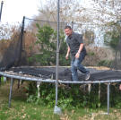 Scott Menaged bounces on a trampoline while partner Lou Amoroso looks on.