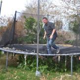 Scott Menaged bounces on a trampoline while partner Lou Amoroso looks on.