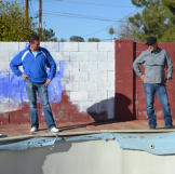 John Ray and Jace Johnson look at a pool in poor condition at a newly purchased property.