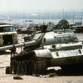 A destroyed Iraqi T-55 main battle tank lies amidst other destroyed vehicles along the highway between Kuwait City and Basra, Iraq, following the retreat of Iraqi forces from Kuwait during Operation Desert Storm.  Watch