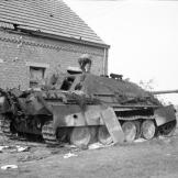 Inspecting an out of commission Panzer in Normandy. Notice the hole just above the second-to-last wheel. Watch video of the
