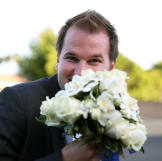 Alan playfully hides behind Kirlyam's bridal bouquet.