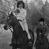 On Nov. 19, 1962, Jackie holds John as she rides a horse at the Kennedy estate in Middleburg, VA. Caroline follows Mom and baby brother on her pony, Macaroni.