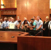 Jen and her coworkers are honored with an award, given by the city of