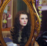 Emily sits at her dressing table to prepare for the day ahead. She wears faux lashes, special contact lenses and long wigs to enhance her doll-like appearance.