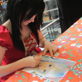 Venus signs autographs for fans at a special event.