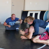 Kody and his friend Brett wrestle while their trainer Sean cheers them