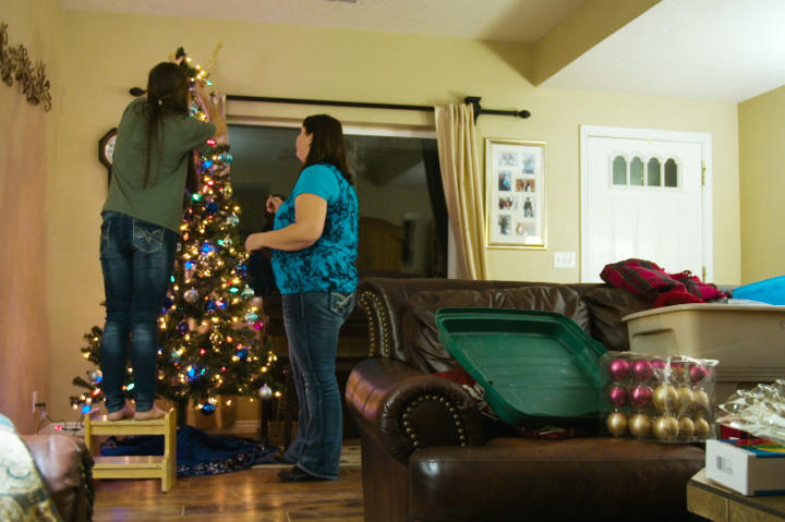Rosemary decorates a Christmas tree with her children.