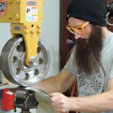 Aaron Kaufman, wearing orange glasses, runs sheet metal through a mach