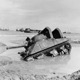 A stuck M4 Sherman tank on a Normandy invasion beach, June 12, 1944. Notice that the tank is fitted with raised air intakes for amphibious use. Watch