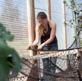 Eve stays at the homestead where she puts netting onto a makeshift pla