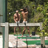 The nudist community is very active; here a few of the residents practice their golf swing at the driving range.