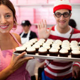 Katherine displays a tray of cupcakes while Waldo waves. Or maybe he's
