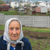 This gypsy elder poses against a concrete wall that separates Roma families from other residents of Ostrovany, eastern Slovakia.