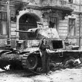 During the courageous yet doomed Warsaw Uprising, a courier poses in front of destroyed Italian Fiat M14/41 tank, August 22, 1944. Watch video of the