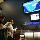 A color map of the world at the Museum of Natural History's earthquake monitoring station shows real-time seismic activity. The exhibit emphasizes the importance of monitoring earthquakes on a daily basis.