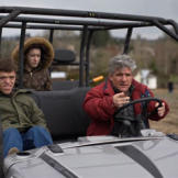 Zach, Molly and Matt ride a golf cart around the family's property in