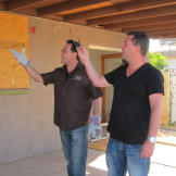 Diamond in the rough? Scott Menaged and Lou Amoroso inspect a back patio that's in need of a renovation.