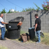 Ed Rosenberg and Scott Menaged search through trash prior to bidding on a house. Evidence of construction materials, such as tile or carpet remnants, offer clues to the interior condition of the home.